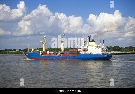 A small freighter ship heads up the Mississippi river in Louisiana. - Stock Photo