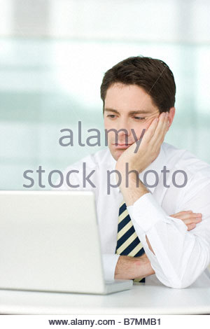 A businessman in an office sitting at laptop, looking bored - Stock Photo
