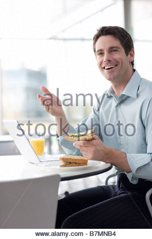 A man in a cafe or office canteen, working on a laptop - Stock Photo