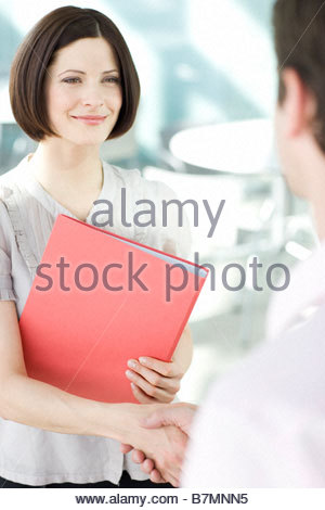 A businesswoman shaking hands with a client - Stock Photo