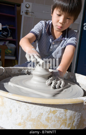 eight year old japanese boy working on a ceramic pot using a wheel - Stock Photo