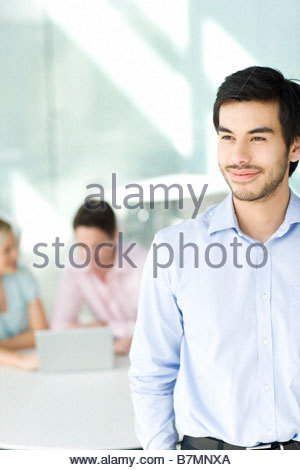 A businessman in an office, two colleagues in background looking at laptop - Stock Photo