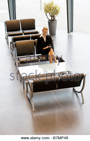 A businesswoman or job candidate sitting in a waiting area - Stock Photo