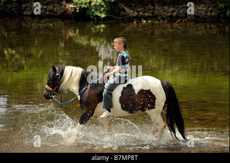 A Romany boy rides bareback on a horse in the River Eden at Appleby in Westmoreland Appleby gypsy horse fair - Stock Photo