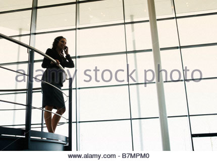 A businesswoman talking on a mobile phone in a modern office building - Stock Photo
