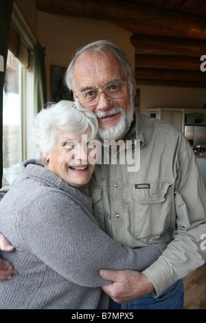 cute elderly married couple in seventies, embracing at home, smiling at camera - Stock Photo