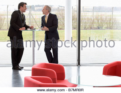 Two businessmen having a meeting in an office building - Stock Photo