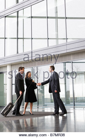 A businessman greeting clients in the foyer of an office building - Stock Photo
