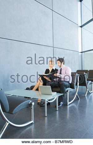 An informal business meeting, a business man and woman reading documents - Stock Photo