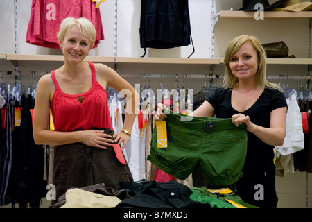 Two women comparing different clothes in shop - Stock Photo