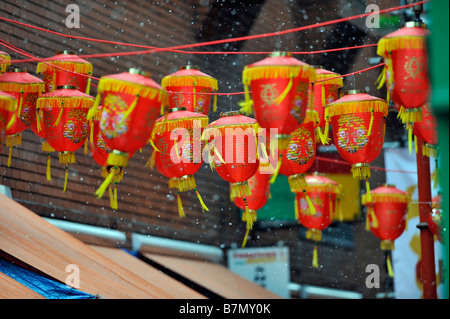 Chinese lanterns in Gerard Street London with snow falling - Stock Photo