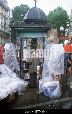 Paris, News-stand in rue de Belleville, near Pyrenees Metro station, draped in plastic sheet as protection against - Stock Photo