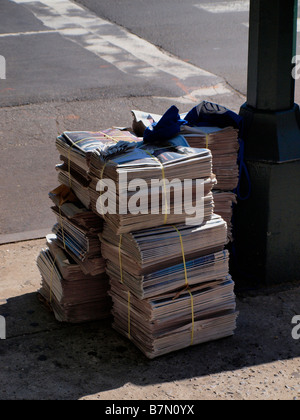 Newspapers stacked for distribution or delivery on a New York City street corner. - Stock Photo
