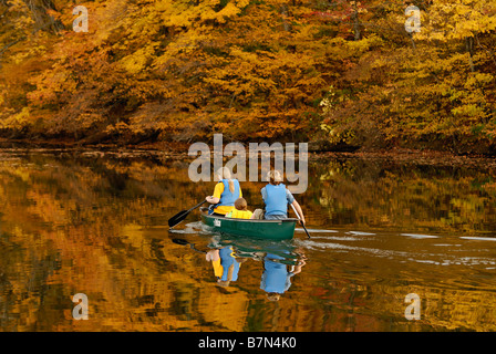Three Teenagers in Canoe on Forested Lake in Autumn at Mount Saint Francis in Floyd County Indiana - Stock Photo