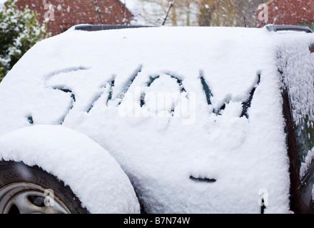 Snow word drawn in fresh snow on a 4x4 car rear windscreen - Stock Photo