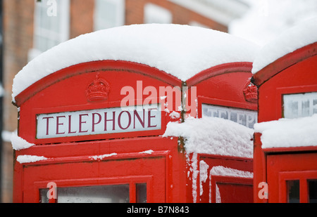 A thick layer of snow on top of red telephone boxes, Richmond, London, UK - Stock Photo