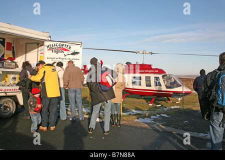 A small helicopter with people waiting to board for a pleasure flight - Stock Photo