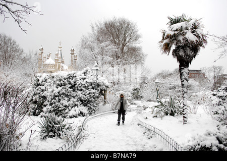 Woman walking in the gardens by the Royal Pavilion in Brighton covered in snow February 2009 - Stock Photo