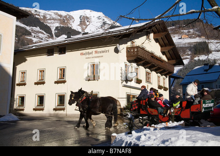 Rauris Austria EU January Group of tourists in a horse drawn sleigh on a tour of this traditional ski resort town - Stock Photo