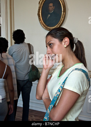 under the stern eye of an ancestor, a pretty Mexican chats on her cellphone while touring Chapultepec castle in - Stock Photo