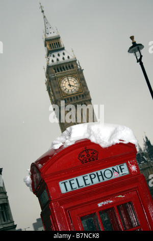 Red phone box covered in snow with big Ben behind - Stock Photo