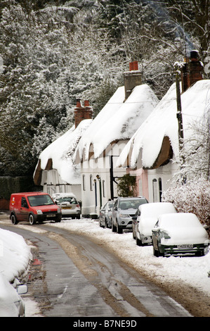 Snow covered cottages in the Hampshire village of Micheldever English winter snow scene Parked cars and postmans - Stock Photo