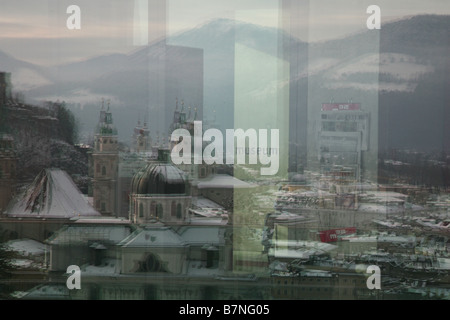 Reflections of Kollegienkirche and Salzburg Cathedral in the windows of Museum der Moderne in Salzburg, Austria. - Stock Photo
