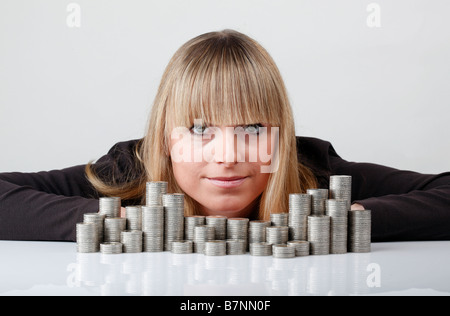 Young woman behind stacked coins - Stock Photo