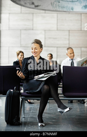 Business woman with a suitcase, waiting - Stock Photo
