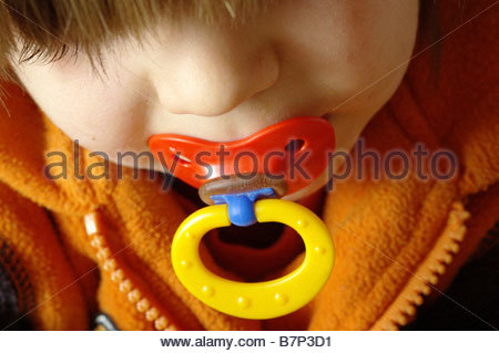 child dummy plastic pacifier close up face - Stock Photo