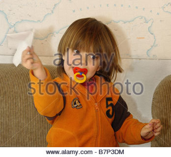 Child throwing a toy aircraft made from folded paper - Stock Photo