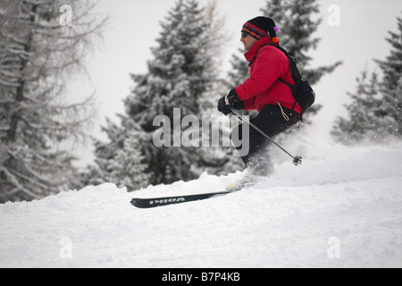 Male skier wearing a red jacket skiing fast down a mountain slope in powder snow on piste in Austrian Alps. Austria, - Stock Photo