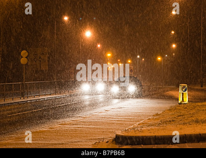Cars driving at night in winter snowing conditions Cwmbran Wales UK - Stock Photo