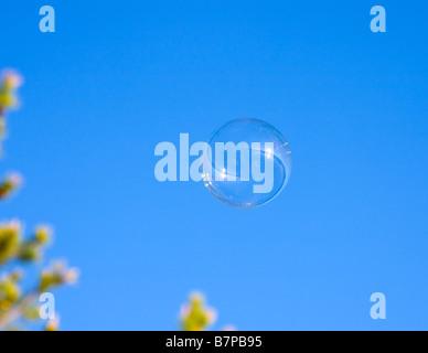 Bubble flies on blue sky background - Stock Photo