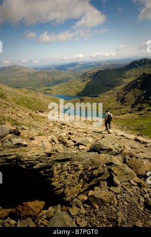 Walker on Path down from mount Snowdon Wales Glaslyh lake and Llyn Llydaw reservoir in distance - Stock Photo