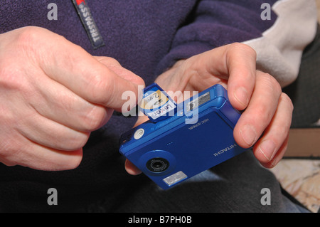 A memory card being inserted into a child's digital camera. - Stock Photo