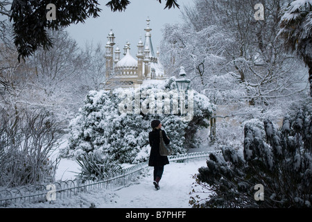 A young woman walks through the snow covered gardens of the Royal Pavilion Brighton in the early morning. - Stock Photo