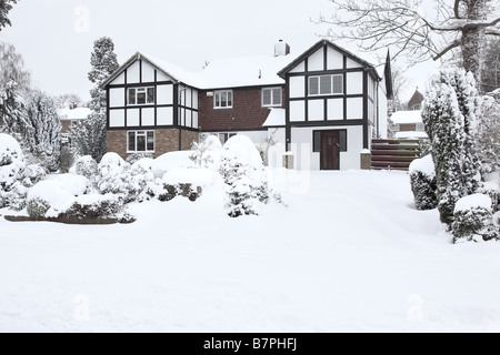 Front view of detached house in winter with a blanket of snow - Stock Photo