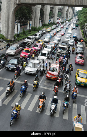 Scooters getting a head start at traffic lights in heavy congestiion Pathumwan district in central Bangkok Thailand - Stock Photo