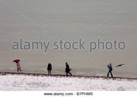 Four people walking along on Brighton beach in snow next to calm sea and a crow - Stock Photo