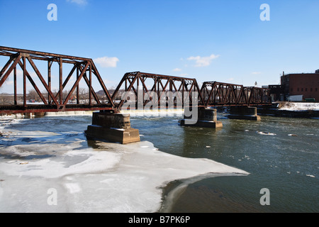 A railroad bridge spans accross an icy river. - Stock Photo
