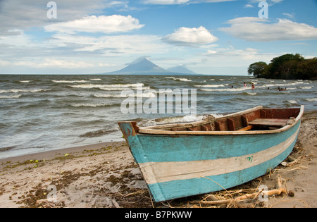 Lake Nicaragua shore north of Rivas with fishing boat, Concepcion and Maderas volcanoes on Ometepe Island in background - Stock Photo