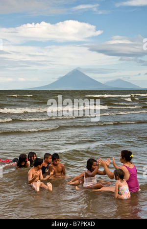 Lake Nicaragua beach north of Rivas with children playing game with their teacher, Concepcion and Maderas volcanoes - Stock Photo