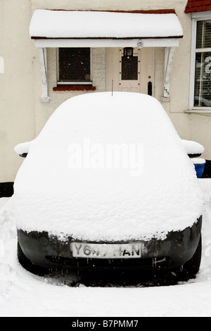 A snow covered car parked in front of a house - Stock Photo
