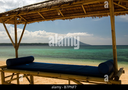 View of Manado Tua volcano from the beach at Siladen Resort and Spa, Sulawesi - Stock Photo