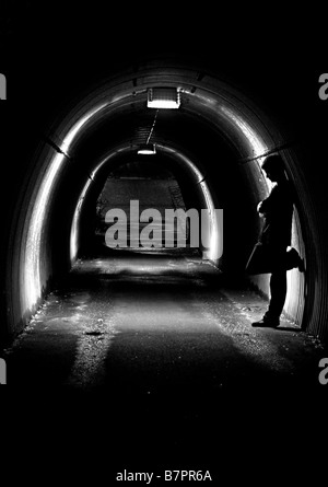 Silhouette of a young man in a tunnel - Stock Photo