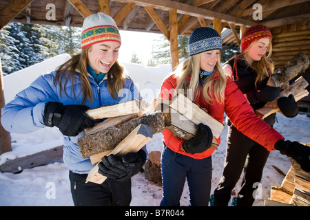 Three young women collect and pile chopped wood near Homer, Alaska during winter. - Stock Photo