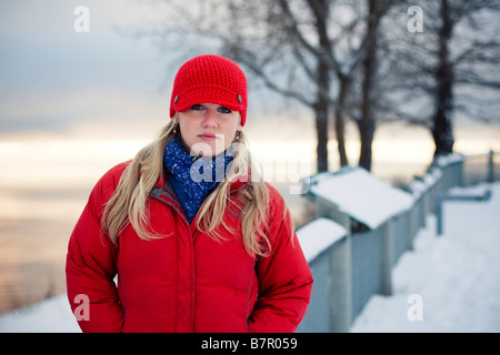 Young woman talks on cell phone at the Baycrest pullout on the sterling highway near Homer, Alaska during Winter - Stock Photo