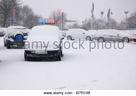 Rows of used cars covered in snow for sale in a secondhand car dealership lot - Stock Photo