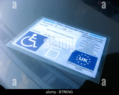 parking card for disabled people known as a disabled badge on the dashboard of a car - Stock Photo